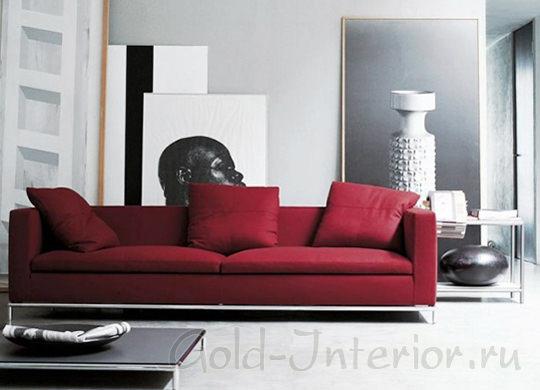 Бордовый диван в окружении ахроматических цветов