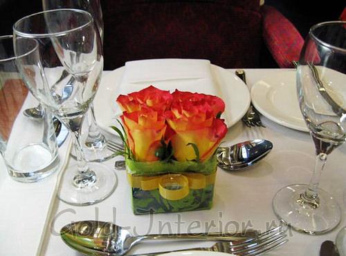 Яркие искусственные цветы на обеденном столе