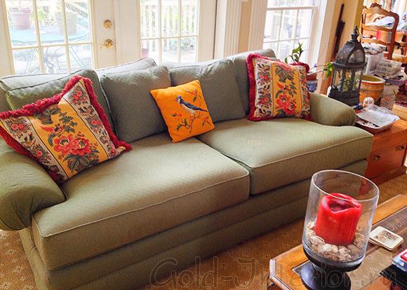 Диван цвета хаки с оранжевыми и красными подушками