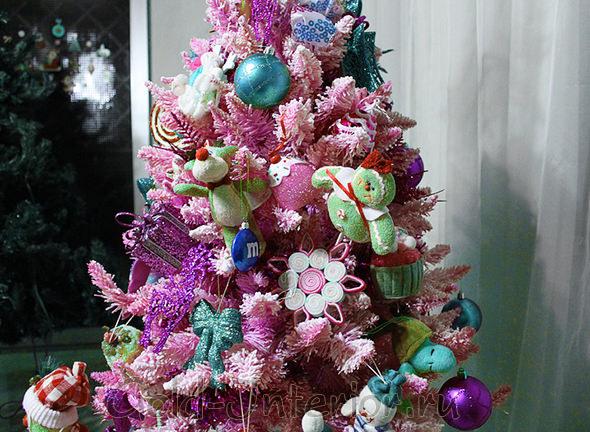 Ёлка розового цвета с новогодними игрушками в интерьере