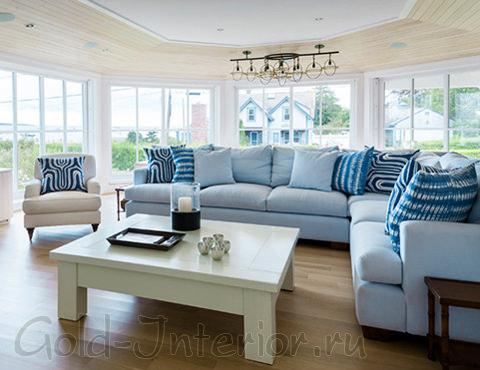 Гостиная и диван голубого цвета выполнены в греческом стиле