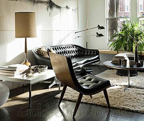 Интерьер с чёрным кожаным диваном у окна