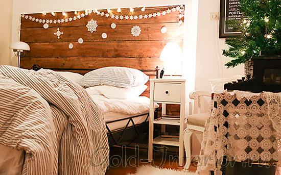 Изголовье кровати украшено новогодней гирляндой