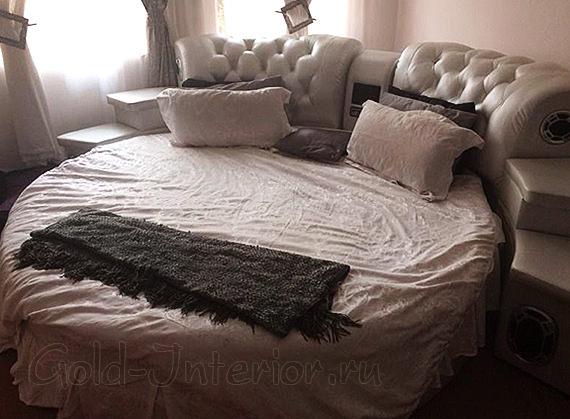 Колонки в изголовье круглой кровати бежевого цвета