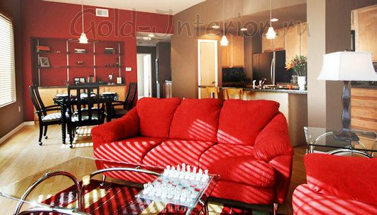 Красный диван и прозрачные поверхности в интерьере гостиной