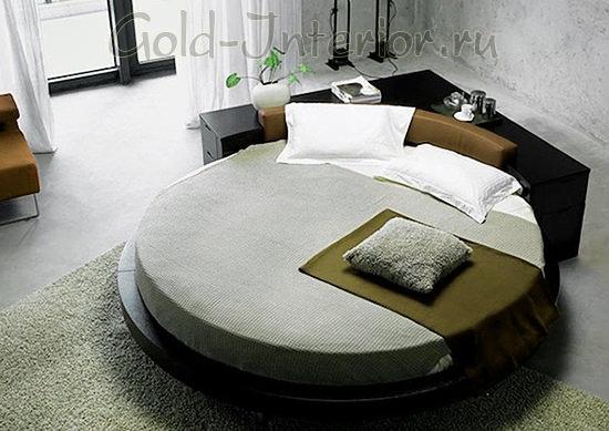Круглая кровать на подиуме и угловой комод