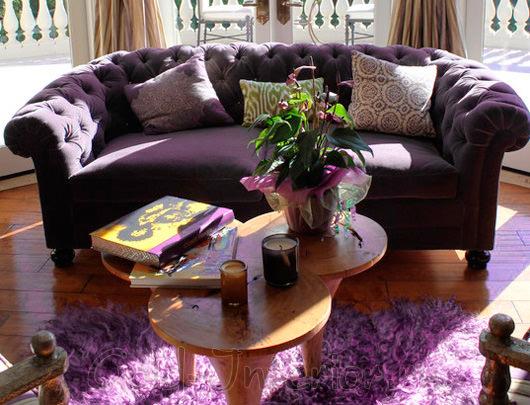 На фотографии интерьер с фиолетовым диваном