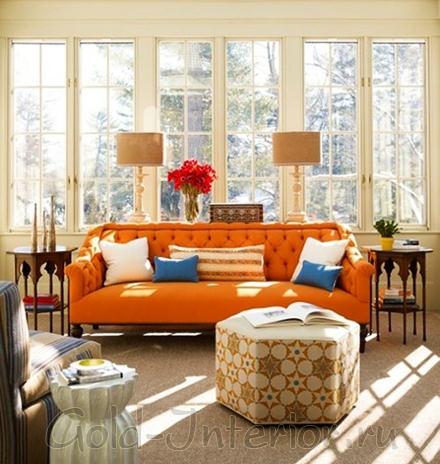 На фото - синие подушки и оранжевый диван