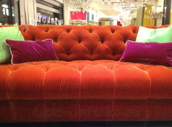 Оранжевый диван с розовыми подушками