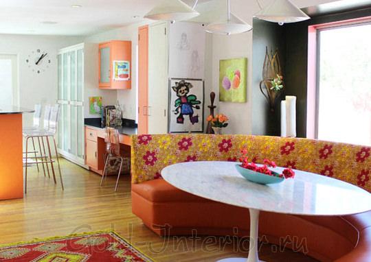 Полукруглый диван оранжевого цвета в декоре кухни