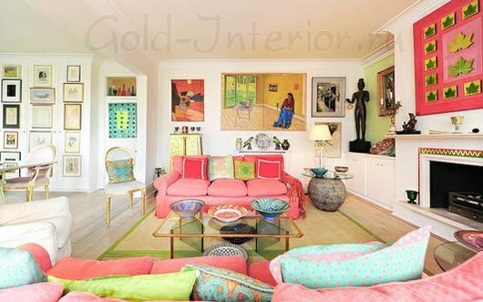 Разноцветный интерьер гостиной с розовым диваном