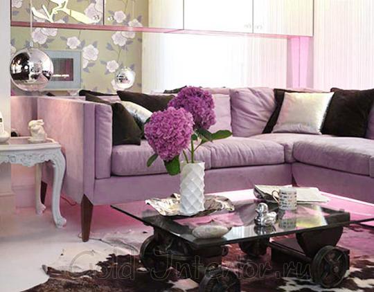 Сочетание лилового дивана и бледно-розовых аксессуаров