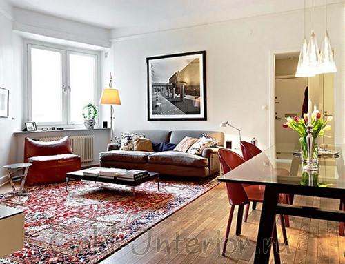 Столовая и гостиная визуально отделены друг от друга красным ковром