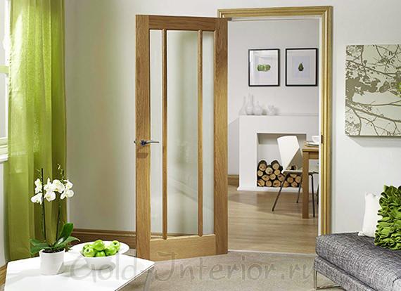 Светлая дверь и зелёные аксессуары в интерьере гостиной