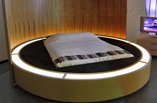 Высокое изголовье из дерева и подсветка на круглой кровати