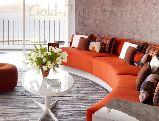Яркий оранжевый диван и аксессуары кондитерских оттенков